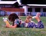 Girl bottlefeeding a lion cub with her feet by John Drysdale
