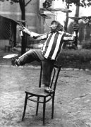 Chimpanzee juggling on a chair by Anonymous