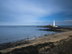 St Mary's lighthouse, over rocky shoreline by Assaf Frank