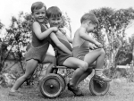 Young boys playing on trike by Mirrorpix