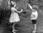 Young girl and boy playing conkers