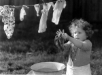 Young girl washing her clothes by Mirrorpix