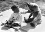 Young toddler playingwith teddy bear by Mirrorpix