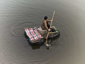Man sitting on rubber tube boat in river, Yangtze River, China by Assaf Frank