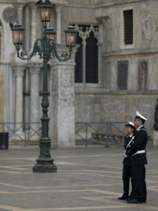 Two policeman standing in San Marco square, Venice by Assaf Frank