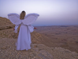 Angel standing on a cliff edge at dusk by Assaf Frank