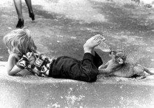 Child bottle-feeding a lion cub by John Drysdale