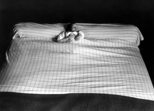 Small child sleeping in a big bed by Bertrand Faucher