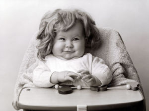 Baby in a high chair wearing a wig by Gerd Pfeiffer