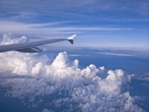 Plane wing and clouds aginst blue skies by Assaf Frank