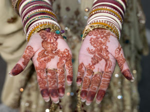 Close-up of woman showing her henna tattooed hands by Assaf Frank
