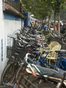 South china, Bicycles parking with people in background by Assaf Frank
