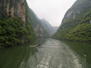 China, Sichuan province, Boat in river by mountains by Assaf Frank