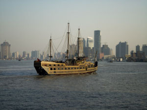 An old boat running on the Huangpu river during the daybreak time. by Assaf Frank