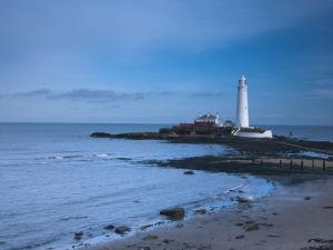 St Mary's lighthouse, over rocky shoreline by Assaf Frank
