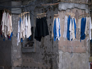 Washing hanging on the street of shanghai by Assaf Frank