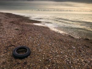 Tire on the beach at sunrise, Littlehumpton England by Assaf Frank