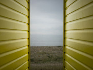 Sea view between two wall of beach huts, Littlehampton England by Assaf Frank