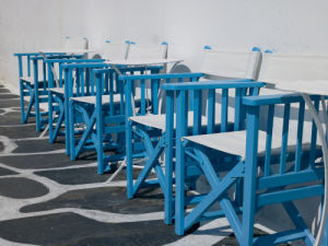 Mykonos Greece, Little venice, Chairs in a row, side view by Assaf Frank
