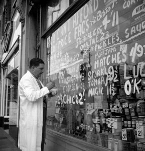 Shopkeeper putting up prices, 1955 by Mirrorpix