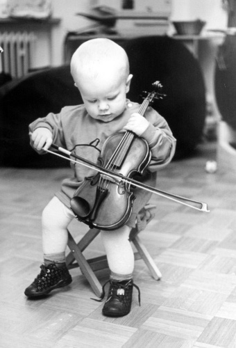 Child plays the violin like a cello by Gerd Pfeiffer