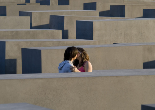 Couple kissing inside the Holocaust memorial Berlin by Heinz Krimmer