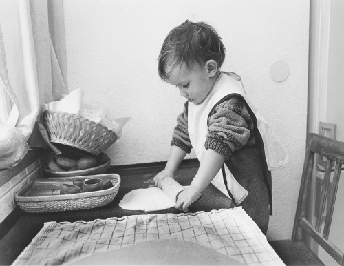 Child rolling pastry by Gerd Pfeiffer
