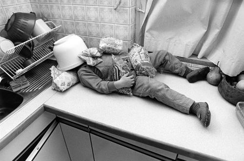 Child sleeping in the kitchen by Gerd Pfeiffer