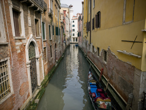 Italy, Boat in canal by building by Assaf Frank