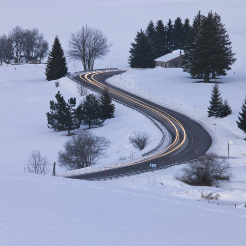 Strip lights on bendy road, snow scenery by Assaf Frank