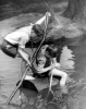 Young boys using large log as a raft by Mirrorpix