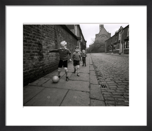 Children playing football by Mirrorpix