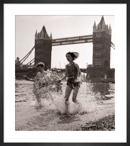 Children paddling on the foreshore below Tower Bridge by Mirrorpix