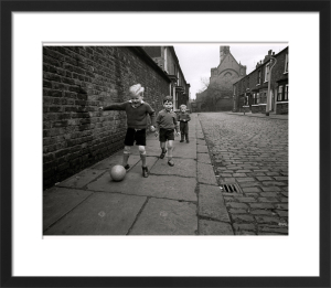 Children playing football by Mirrorpix